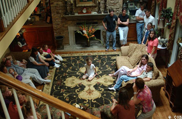 SOME OF THE MEMBERS OF THE CARITAS COMMUNITY ARE GATHERED IN THE LIVING ROOM WHERE THE DRAMATIC APPARITION DESCRIBED HERE WOULD TAKE PLACE ON JULY 31, 2005. THIS PICTURE WAS TAKEN ON JULY 24, 2005 JUST AFTER MARIJA'S APPARITION TOOK PLACE IN THE BEDROOM. MARIJA CAN BE SEEN IN THE LOWER RIGHT HAND CORNER OF THE ROOM, SPEAKING TO SOME OF THE COMMUNITY.