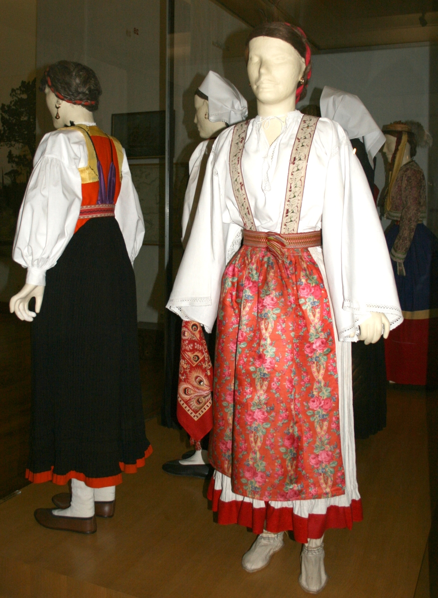CROATIAN NATIONAL DRESS FROM THE ISLAND OF OLIB THE ISLANDS OF CROATIA HAVE THE MOST VARIATION IN DRESS DUE TO THEIR GEOGRAPHIC DISTANCE AND ISOLATION FROM ONE ANOTHER. THEY FIND MORE SIMILARITY WITH DALMATIA AND ISTRIA, BUT MANY HAVE THEIR OWN UNIQUE STYLES NOT SEEN ELSEWHERE.  FOR EXAMPLE, THE NATIONAL COSTUME FROM THE ISLAND OF PAG HAS ITS ORIGINS IN THE FIFTEENTH CENTURY, AND IS CHARACTERIZED BY THE INTRICATE LACE THAT DECORATES THE FRONT PART OF BLOUSES AND THE EDGES OF KERCHIEFS. THE FAMOUS LACEWORK OF PAG IS RENOWNED FOR ITS PRECISION AND BEAUTY, AND IS THE MOST PROMINENT PART OF THE COSTUME APART FROM THE LARGE WHITE HEADDRESSES WORN BY THE WOMEN OF THE ISLAND. WOMEN WEAR LONG-SLEEVED BLOUSES AND FULL PLEATED SKIRTS (USUALLY GOLD OR RED IN COLOR) WITH A RED SILK SCARF TIED AROUND THEIR WAIST. THE MEN WEAR VESTS OVER THEIR SHIRTS WITH FORM-FITTING TROUSERS WITH A RED SILK HANDKERCHIEF WORN AROUND THE WAIST AND RED HATS.