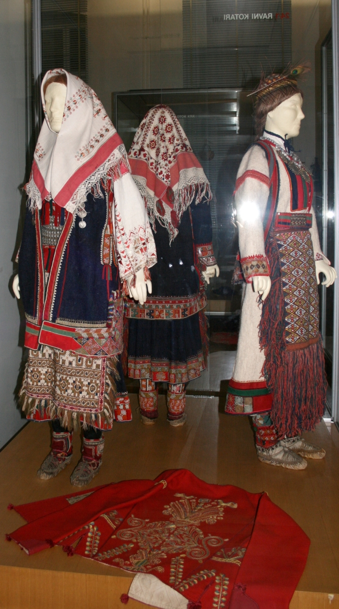 COSTUME FROM NORTHERN DALMATIA (RAVNI KOTARI)DALMATIAN COSTUME DALMATIAN COSTUME VARIES FROM WITHIN ITS OWN REGION; WHILE THE COASTAL AREAS ARE ADRIATIC AND COASTAL IN INFLUENCE, THE INNER AREA, CALLED DALMATINSKA ZAGORA, SHOWS THE DINARIC INFLUENCE SIMILAR TO THE STYLE OF LIKA AND HERZEGOVINA.  PERHAPS THE MOST FAMOUS EXAMPLE OF DALMATIAN ZAGORA COSTUME COMES FROM THE SMALL TOWN OF VRLIKA, RICH IN DANCE AND TRADITION STILL CARRIED ON TODAY. BOTH MEN AND WOMEN'S DRESS WEAR IS CHARACTERIZED BY MULTIPLE SUBJECTS OF CLOTHING OVER ANOTHER. FOR MEN, THE COSTUME CONSISTS OF CAREFULLY CHOSEN PIECES WORN OVER EACH OTHER: A RED SASH IS TIED AROUND DARK PANTS WITH A FRINGE OF THREADS HANGING FROM THE BELT IN RED, BLUE, OR GREEN COLORS. DUE TO CENTURIES OF MILITARY MENTALITY, A SPECIAL LEATHER BELT IS WORN TO CARRY WEAPONS. OVER THE SHIRT IS A DECORATED TUNIC, ELABORATE IN DESIGN AND CUSTOM-MADE FRINGE. THE VEST THAT IS WORN IS VASTLY DECORATED WITH GOLD AND RED EMBROIDERY AND PATTERNS AND DESIGNS, WITH DIFFERENT STYLES OR MATERIAL AND CUT DEPENDING ON THE SEASONAL WEATHER. MUCH LIKE THE MEN, THE WOMEN'S DRESS CONSISTS OF CLOTHING WORN OVER MORE CLOTHING: A WHITE BLOUSE, SKIRT OR TUNIC IS MOST COMMON, WITH A COLORFUL APRON CONSISTING OF COMPLICATED GEOMETRIC PATTERNS AND FRINGE WORN OVER, AS WELL AS A RED VEST WITH GOLD STITCHING MADE IN A WAY TO MAKE IT STAND OUT FROM THE WHITE BLOUSE. JEWELLERY CONSISTS MAINLY OF BEADS WORN AROUND THE NECK AND SILVER COINS ADORNED AROUND THE COSTUME. BOTH MEN AND WOMEN WEAR RED FELT PILLBOX CAPS (BARETA OR CRVENKAPA), WITH A WHITE HABIT ATTACHED TO THE WOMEN'S'.  FROM THE COAST, THE NATIONAL COSTUME OF DUBROVNIK CONSISTS MAINLY OF WHITE, BLACK, GOLD, AND RED COLORS. BOTH MEN AND WOMEN WEAR VESTS RICH WITH GOLD EMBROIDERY WHILE THE WOMEN WEAR THE RECOGNIZABLE GOLD TASSELS DECORATING THE FRONT BLOUSE AND FINE JEWELRY SUCH AS EARRINGS, NECKLACES AND HAIR CLIPS. MEN AND WOMEN USUALLY WEAR WHITE OR BLACK TROUSERS OR SKIRTS RESPECTIVELY.