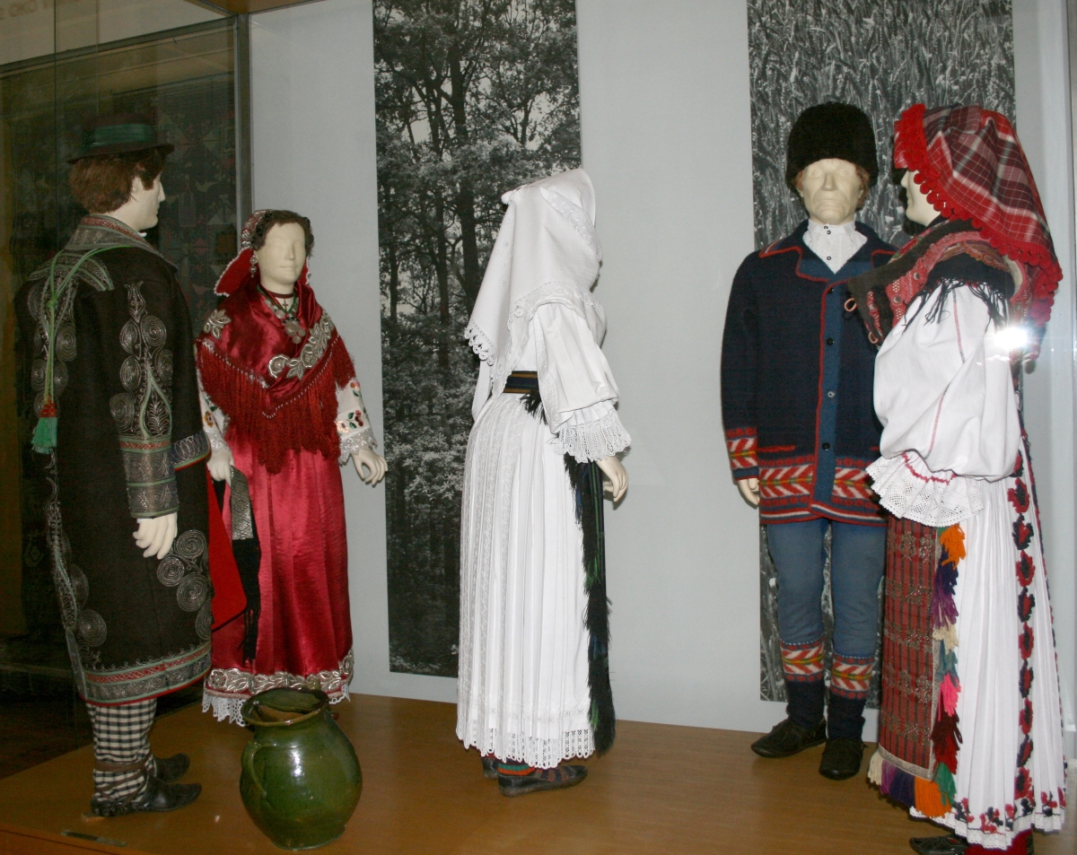 CROATIAN NATIONAL DRESS FROM VINKOVCI SLAVONIA AND BARANYA  BOTH SLAVONIA AND BARANYA ARE LOCATED IN THE EAST, AND ARE ASSOCIATED WITH THE PANNONIAN STYLE OF DRESS. IN SLAVONIA, THE COSTUMES TEND TO BE VERY ELABORATE, WITH FLORAL DESIGNS AND CLOTHING WITH SILK OR WOOL, FANCY EMBROIDERY, DECORATIVE SILK RIBBONS AND BOWS, LACEWORK, GOLD OR SILVER JEWELRY, CORALS, AMBER NECKLACES AND PEARLS FOR THE WOMEN. THE COLORS OF THE DRESSES TEND TO BE BRIGHT AND NUMEROUS, WITH COLORS RANGING FROM GOLD, RED, BLUE, WHITE, AND BLACK ALL IN ONE COSTUME. THE TOP SHIRT, OR ODNJICA, OF THE COSTUME HAS FRINGED-WING SLEEVES, WHICH IS GENERALLY ASSOCIATED WITH THE PANNONIAN STYLE.  FOR THE MEN, THEY TEND TO WEAR NOT AS MANY COLORS FOR THE SHIRT AND PANTS, BUT OFTEN WEAR THICK COATS OR VESTS WITH DESIGNS AND PATTENS STITCHED ON AND FANCY EMBROIDERY LIKE THE WOMEN. THEIR SLEEVES MIGHT HAVE A SLIGHT RUFFLE AT THE END, BUT NOT AS MUCH AS THE WOMEN'S' IN BARANJA, A PART OF THE MEN'S COSTUME IS A SMALL APRON THAT IS WORN OVER THE TROUSERS THAT RANGES IN COLOR AND DESIGN.  CROATIAN NATIONAL DRESS FROM VINKOVCI