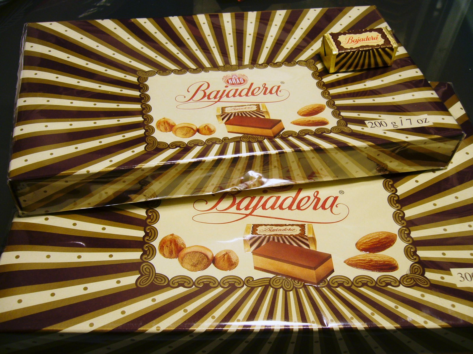 "BAJADERA THIS WORLD KNOWN DELICIOUS NOUGAT, PRODUCED BY KRAŠ, CONSISTS OF A CREAMY HAZELNUT AND ALMOND FILLING BETWEEN TWO LAYERS OF MILK CHOCOLATE. A BOX OF THESE TASTY CHOCOLATES WITH ITS DISTINCTIVE GOLD AND YELLOW DESIGN IS A TRUE CROATIAN CLASSIC, GIFTED AS A TOKEN OF APPRECIATION WHEN VISITING.   BAJADERA CHOCOLATES  YOU EVER TRIED ONE OF THESE?  IF YOU SEE ONE YOU MIGHT WANT TO. TASTY.  ITS A PRODUCT OF CROATIA AND YOU CAN LOOK FOR IT IN THOSE LITTLE EURO MARTS.   THE MAGIC OF A SUPREME PLEASURE  BAJADERA IS ONE OF KRAŠ'S (KRAS FOOD INDUSTRY) BEST KNOWN BRANDS ON THE CROATIAN MARKET. THIS EXQUISITE CHOCOLATE COMBINES A CENTRAL EUROPEAN CONFECTIONER'S ART WITH THE ORIENTAL EXTRAVAGANCE OF FLAVOURS. BAJADERA IS THE QUEEN OF CHOCOLATES, FINE NOUGAT BLENDED WITH ALMONDS WHICH GIVES A UNIQUE, RECOGNIZABLE FLAVOUR. BAJADERA IS THE FIRST CROATIAN CONFECTIONERY PRODUCT TO BE GRANTED THE ""CROATIAN CREATION"" LABEL."