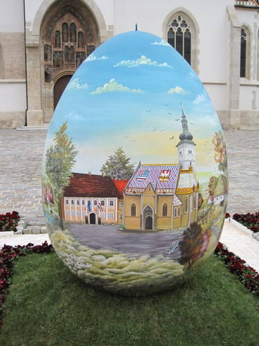 "GIANT EASTER EGG  EASTER EGG IN FRONT OF ZAGREB'S ST. MARK'S CHURCH THIS GIANT EASTER EGG IN FRONT OF ST. MARK'S CHURCH IN ZAGREB STANDS IN THE MIDDLE OF THE SQUARE. THE EGG DEPICTS THE CHURCH WITH THE SYMBOL OF ZAGREB PICKED OUT IN TILES UPON ITS ROOF. THE EGG WAS PAINTED BY ARTISTS IN THE LOCAL ""NAIVE"" STYLE."